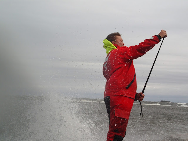 Pelastautumispukuinen henkilö säätää selfie-kepin päässä olevaa Gopro-kameraa valtavassa aallokossa