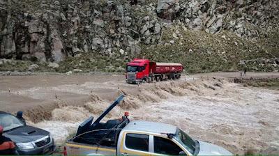 Caminhão tenta transpor uma ponte prejudicada pela elevação do nível das águas de um rio.