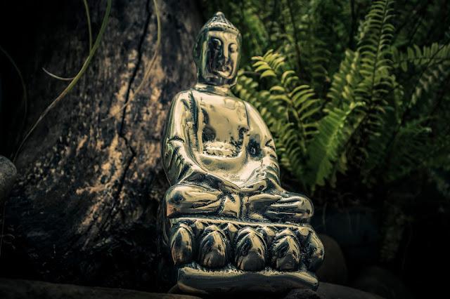 escultura de buda em ferro fundido meditando ao lado de árvore