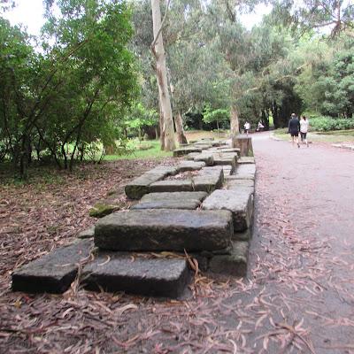 muro de granito e pessoas passeando no parque