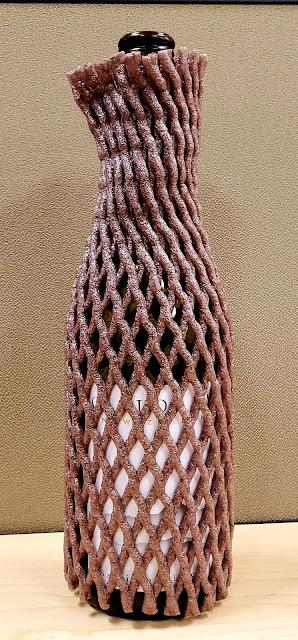 Bottle wrapped in a net sleeve  ©LeDomduVin 2020