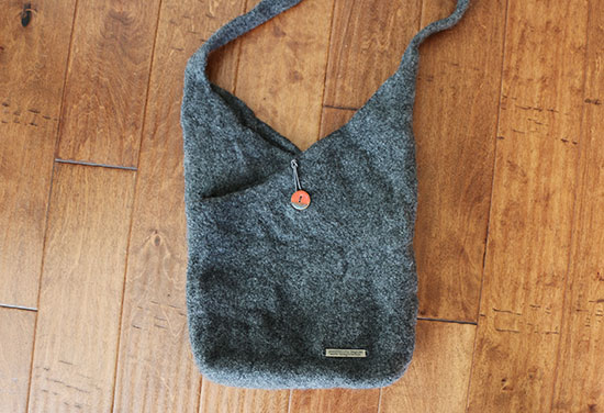 Dark gray fulled wool purse with red handmade button and silver metal label on a dark wood background.