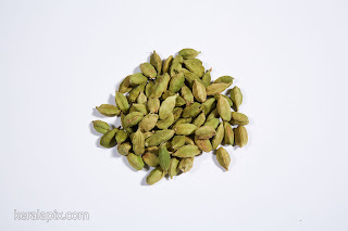 Green cardamom spice in a white background