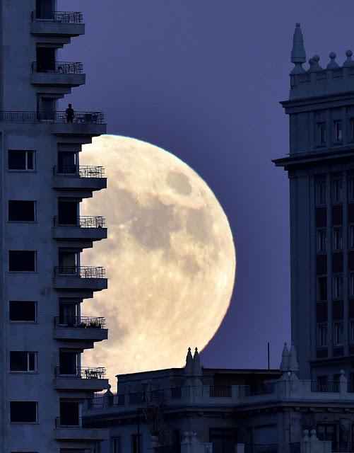 Một người đang đứng từ ban công của một tòa nhà và ngắm nhìn Trăng tròn đang mọc lên. Hình ảnh này sử dụng một kỹ thuật nhiếp ảnh, mà người chụp đứng từ xa và phóng to lên, nên Mặt Trăng trông rất lớn và không đúng với thực tế. Hình ảnh: Gerard Julien/Getty Images.