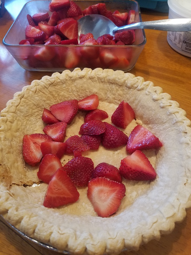 this is a pie crust lined with fresh strawberries and a bowl of sliced berries is in the back of it