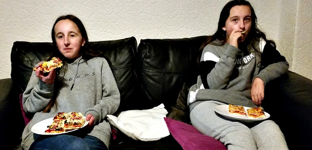 My girls on the sofa eating homemade pizza.