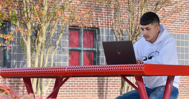 student sits at a computer in front of fall trees
