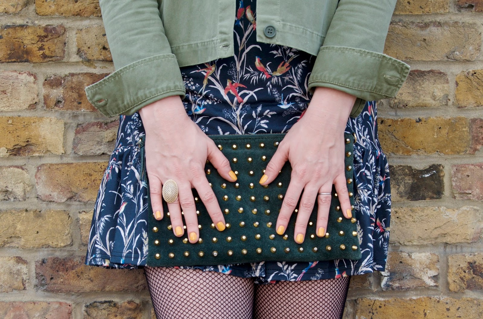 yellow nail polish, floral dress, green jacket, green suede studded clutch and fishnet tights