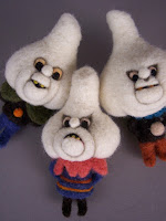Three felt ornaments. They have white heads shaped to look like garlic and are dressed in colorful. They don't look too happy.