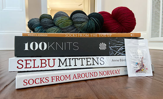A stack of four knitting books with two skeins of sock yarn on top and a small packet of stitch markers to the side.