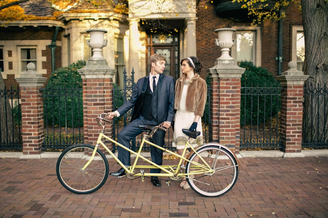man in a suit and a woman in a dress and fur coat stand behind a yellow tandem bike in front of the inn at irwin gardens
