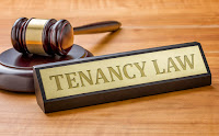 "A wood and metal plaque that says, ""tenancy law"" in capital letters in front of a judge's gavel. Both are on a wooden surface."