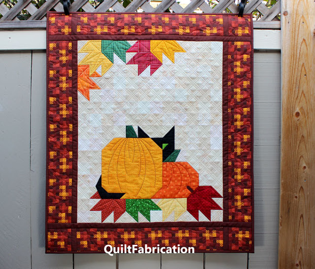 black kitty peeking from behind two pumpkins in a wall hanging pattern by QuiltFabrication