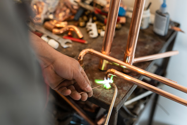 man welding with copper