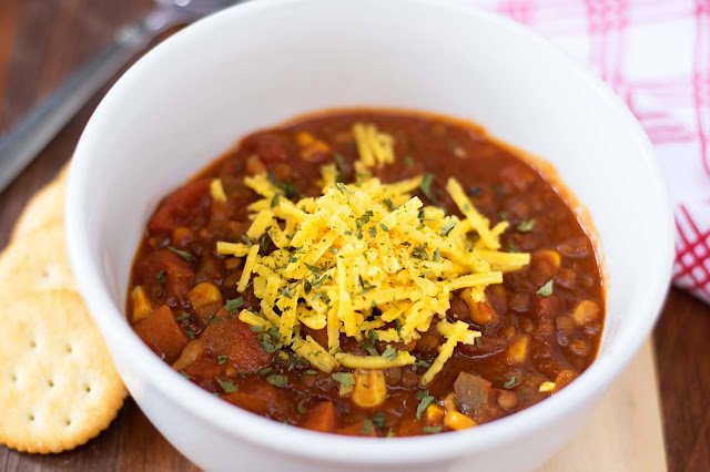 The Perfect Chili, finished, in a white bowl, topped with cheese, and crackers on the side.