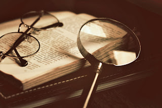 Spectacles and a magnifying glass lying on an open book