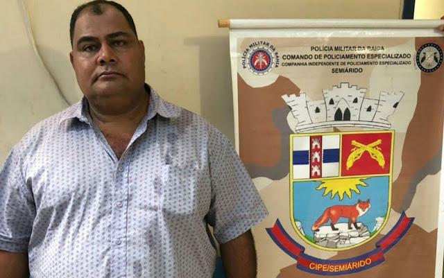 Foto do homem na delegacia, do lado do logo da PM