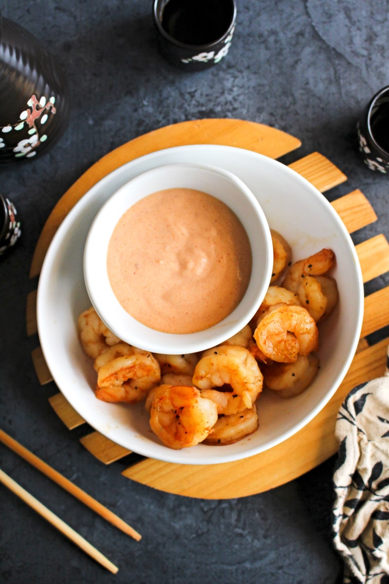 Top view of yum yum sauce in a white bowl sitting in a larger white bowl filled with cooked shrimp.  Bowl is on a wood rack sitting on a grey background.