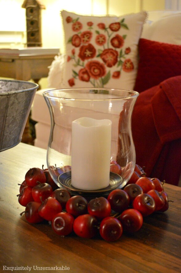 Apple ring around candle and glass hurricane on table in living room