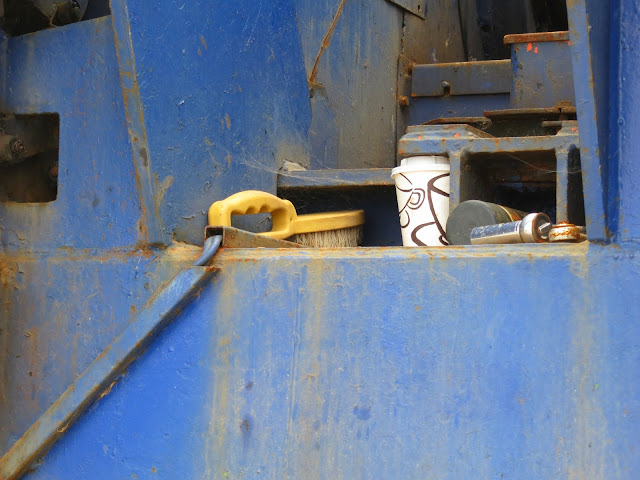 Coffee mug and yellow handed brush in blue container? machine? can't remember!