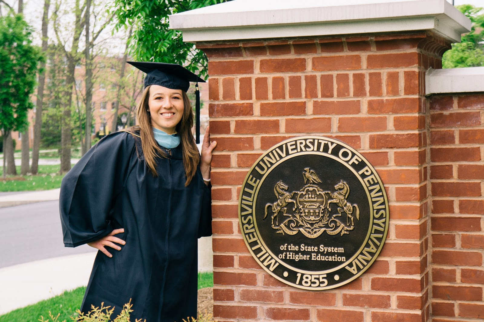 Graduate in her cap and gown standing next to the seal of Millersville University