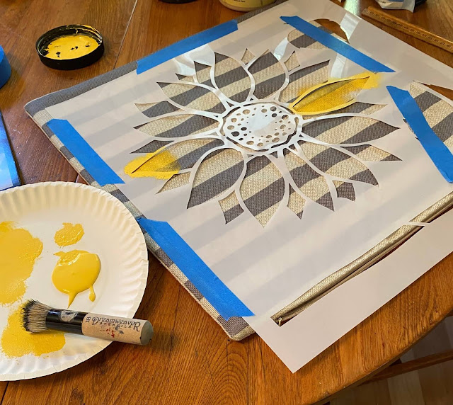 Photo of a sunflower stencil taped to a pillow cover.
