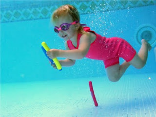 Picture of a child underwater with childrens goggles on picking up weighted pool toys: