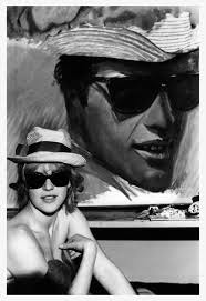Pauline Boty poses bare shouldered with her painting With Love to Jean-Paul Belmondo
