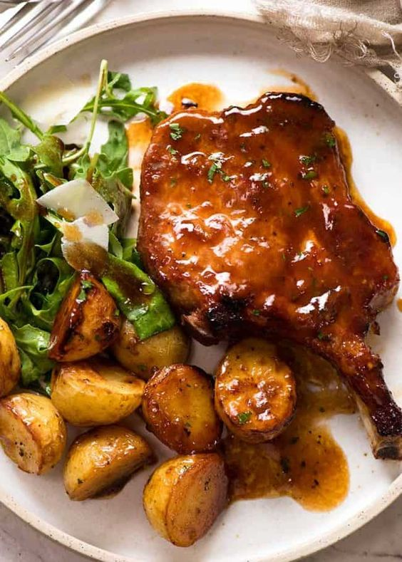 Overhead photo of Oven Baked Pork Chops with potatoes, with a side of Rocket with Parmesan and Balsamic
