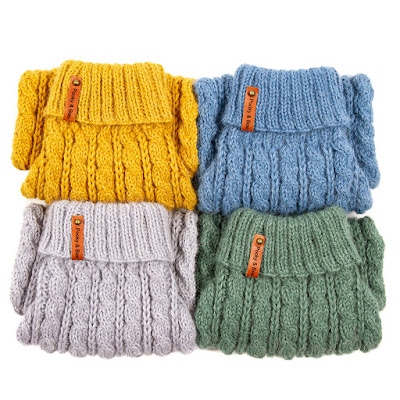 folded hand-knitted cable jumpers in four colours