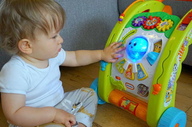 toddler looking at the little tikes light 'n' go walker
