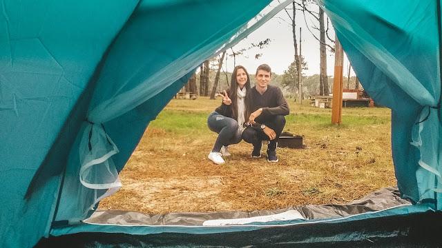 Casal em frente à barraca do acampamento