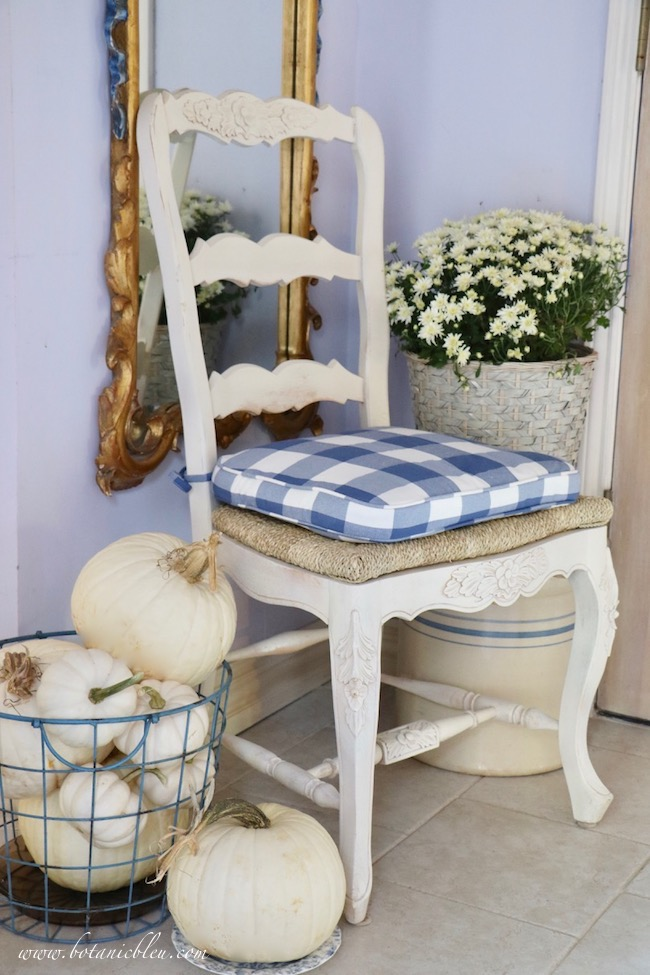 Cottage style Fall foyer with white pumpkins, white French ladderback chair, and white mums
