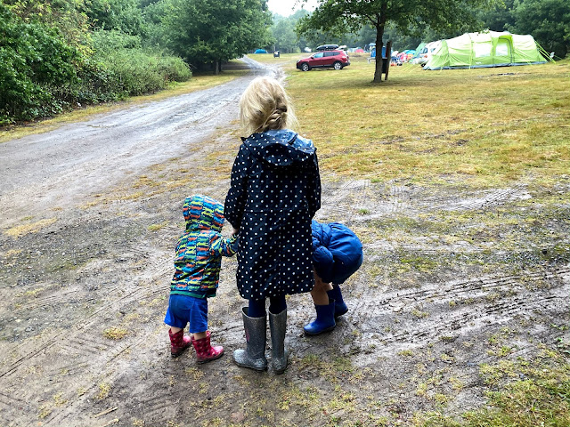 3 children in rain coats and wellies on a muddy campsite