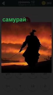 на закате стоит силуэт самурая с саблей в руках