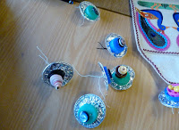 Peacock's tail eyes made from concentric circles of silver foil, plastic, milk bottle tops, buttons and beads