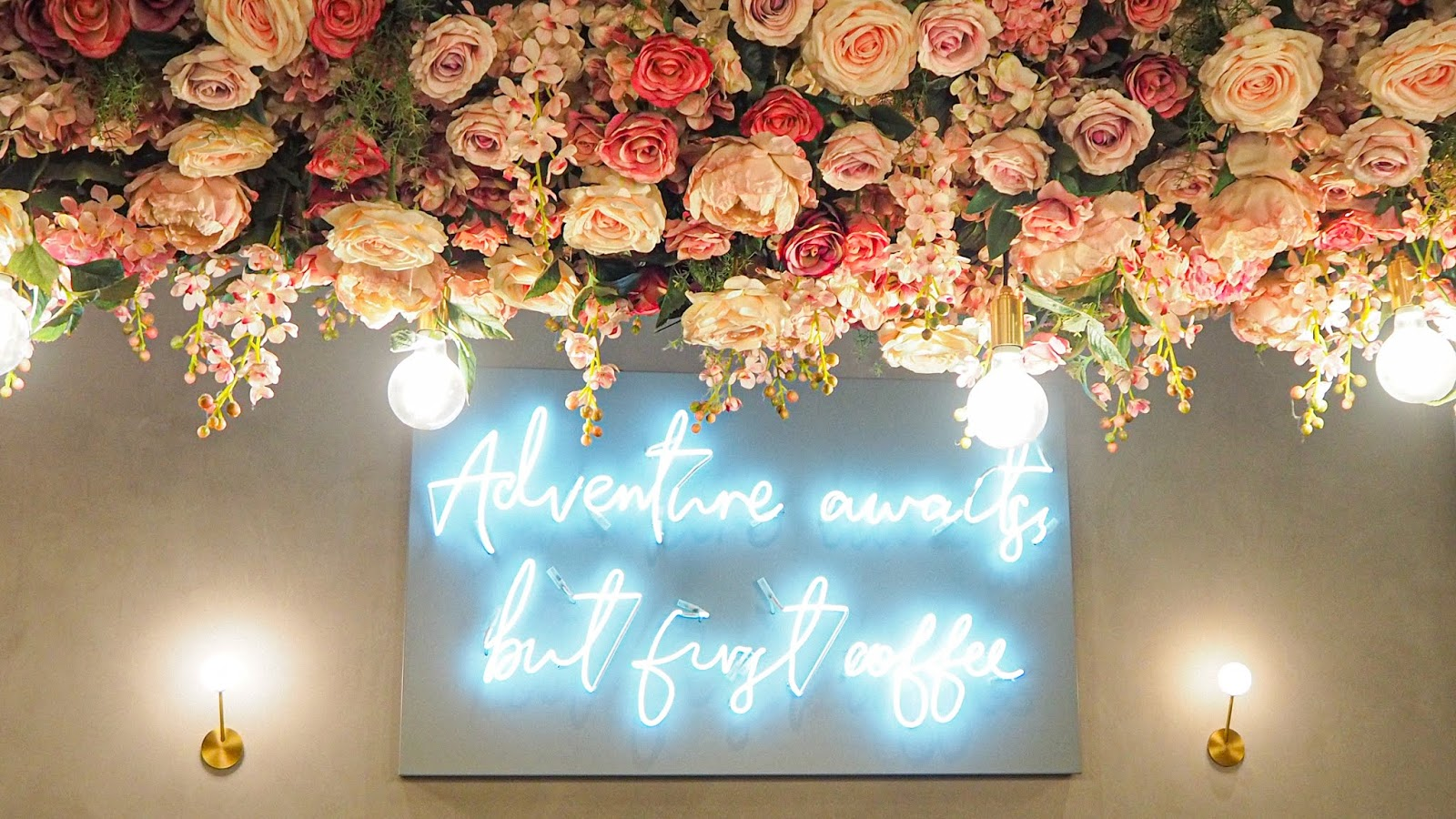 Neon Sign that says Adventure Awaits, But First Coffee with flowers overhead