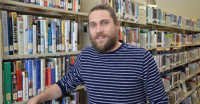 man in front of library books