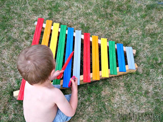 Child playing on a homemade xylophone for kids
