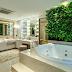 Banheiro neutro e dourado com banheira, jardim vertical e bancada de maquiagem em ônix!