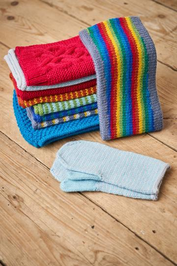 A pile of multi-coloured knitting resting on a wooden table next to a pair of hand-knitted mittens