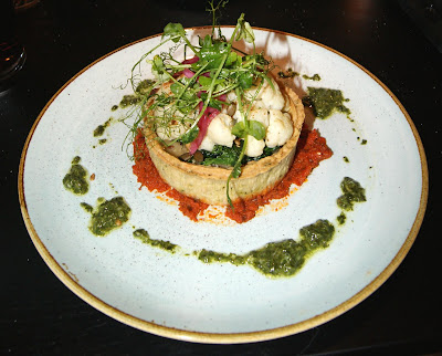 Moroccan-Inspired Cauliflower Tart in a kale and thyme pastry case, with a baby spinach and leek based, topped with seeds and a herb dressing, served with a slow-roased tomato sauce