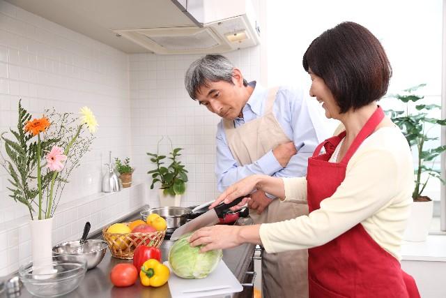 キッチンで調理する夫婦
