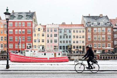 Maisons colorées de Copenhague, homme qui passe en vélo et quais recouverts de neige