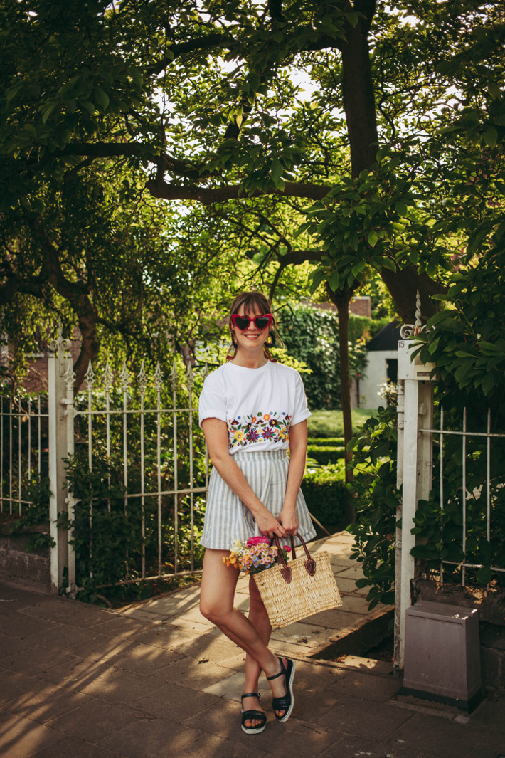 Striped shorts, fringe sandals, flowers in basket, embroidered tee, heart shaped glasses