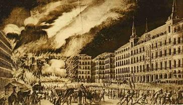 panorámica de la plaza con un lateral en llamas, humareda y numerosas tropas en formación, algunos soldados evacúan heridos.