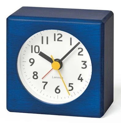 square blue alarm clock, round white dial, yellow second hand, red alarm indicator