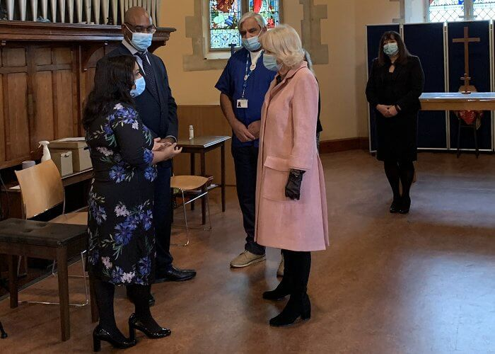 The Duchess met with those involved in the vaccination process, including NHS staff, volunteers and representatives. Pink wool coat and black boot