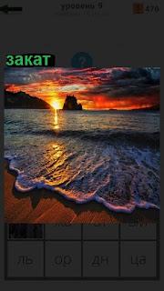 Происходит закат на море во время прибоя, накатываются волны
