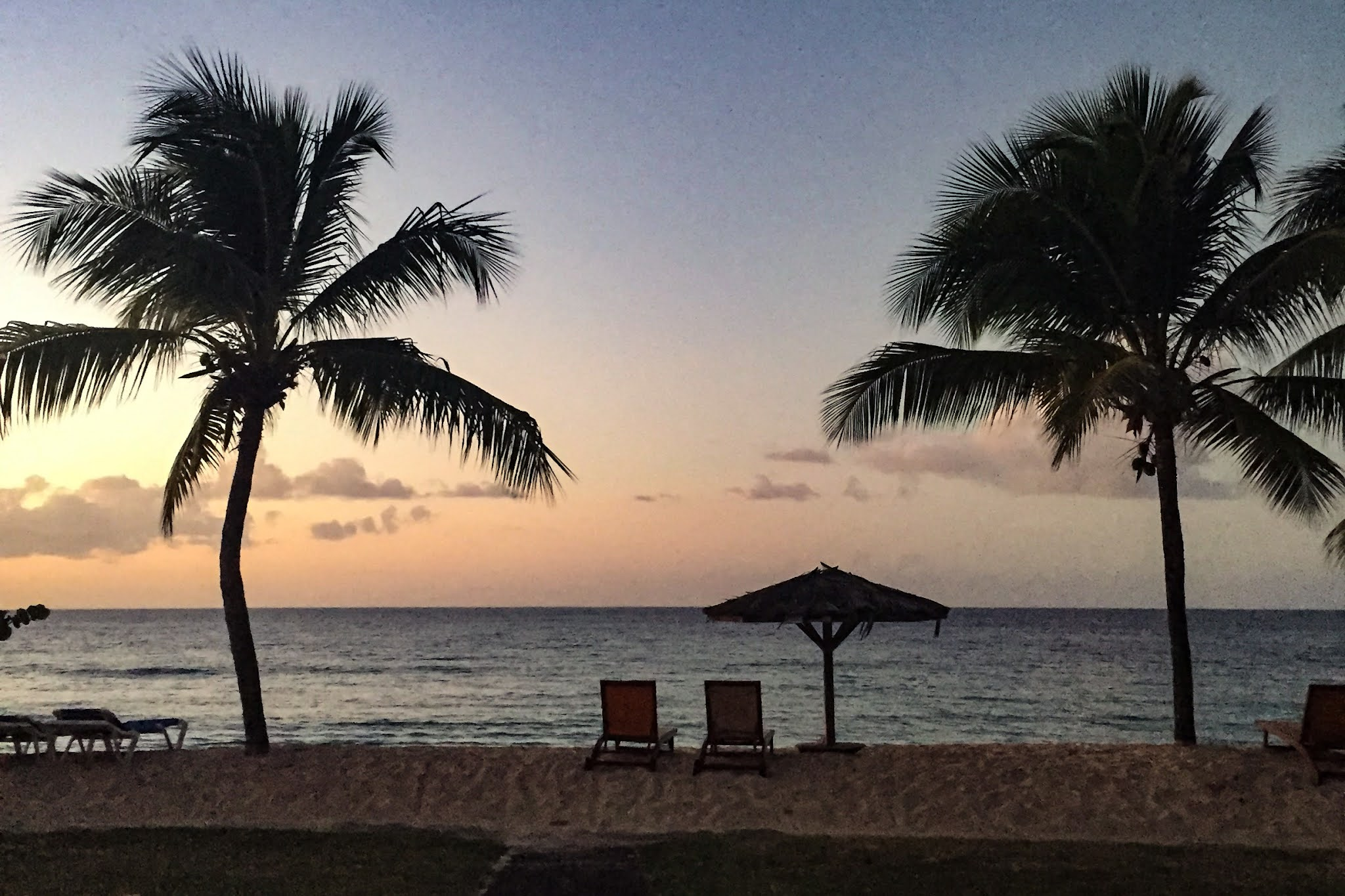 A sunset on a beach in Grenada showing palm trees an umbrella and seats